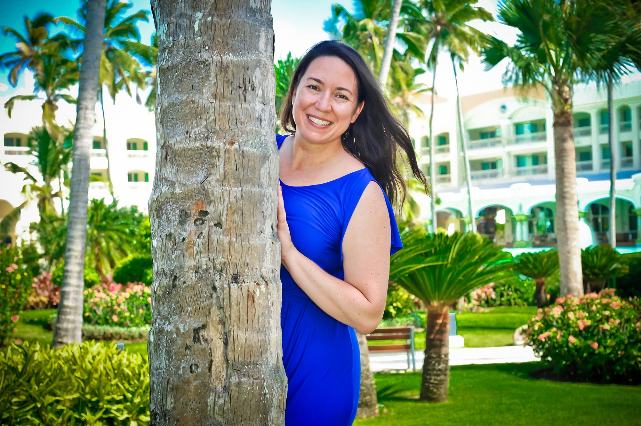 Woman (Colette) in a blue dress leaning out from behind a palm tree at a hotel in the Caribbean.